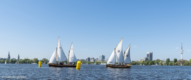 Zwei Jugendwanderkutter beim Hamburger Jugendseglertreffen auf der Alster. Die beiden Boote segeln gerade mit Wind von hinten durch das Leegate.