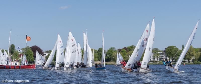 Start der Piratenklasse beim Hamburger Jugendseglertreffen auf der Alster in Hamburg. Auf der linken Seite ist das rote Startschiff zu sehen. Etwa ein dutzend Boote sind an der Startlinie aufgereiht.