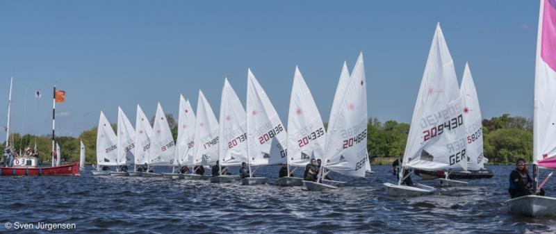 Start der Laserklasse beim Hamburger Jugendseglertreffen auf der Alster in Hamburg. Auf der linken Seite ist das rote Startschiff zu sehen. Etwa zwanzig Boote sind an der Startlinie aufgereiht.