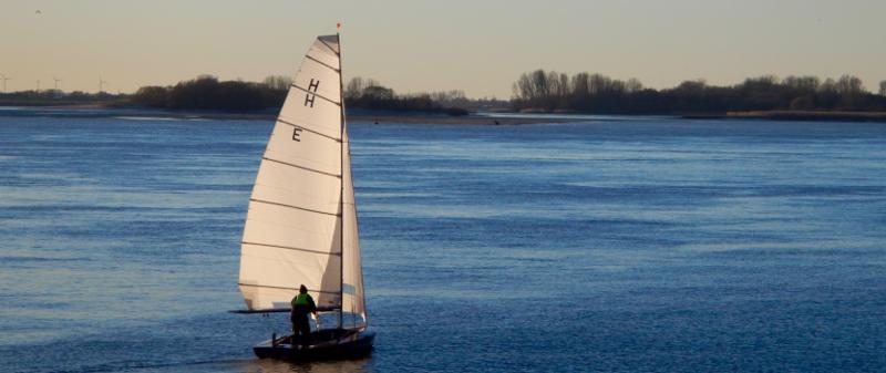 Eine H-Jolle segelt mit nur einer Person Besatzung und leichter Briese auf dem Mühlenberger Loch und den Seitenarmen der Elbe. Im Hintergrund ist in abendlicher Stimmung eine Sandbank zu sehen.
